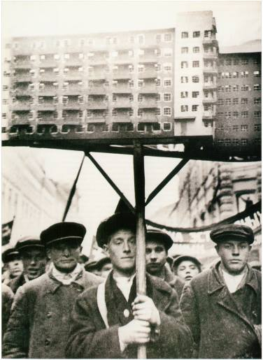 soviet-builders-marching-with-models-of-avant-garde-houses1931
